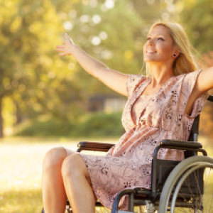 Disabled Young Woman in Wheelchair Enjoying outdoors.