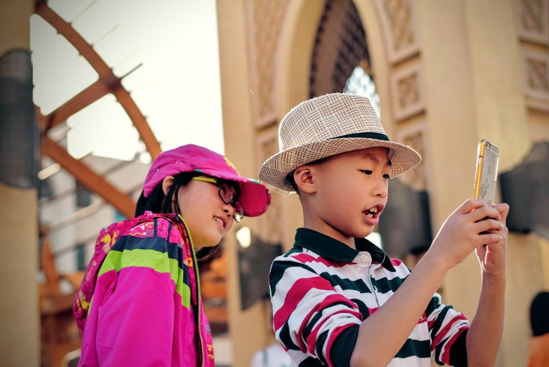 due bambini usano un cellulare per mappare le barriere architettoniche di una città. sembra che giochino